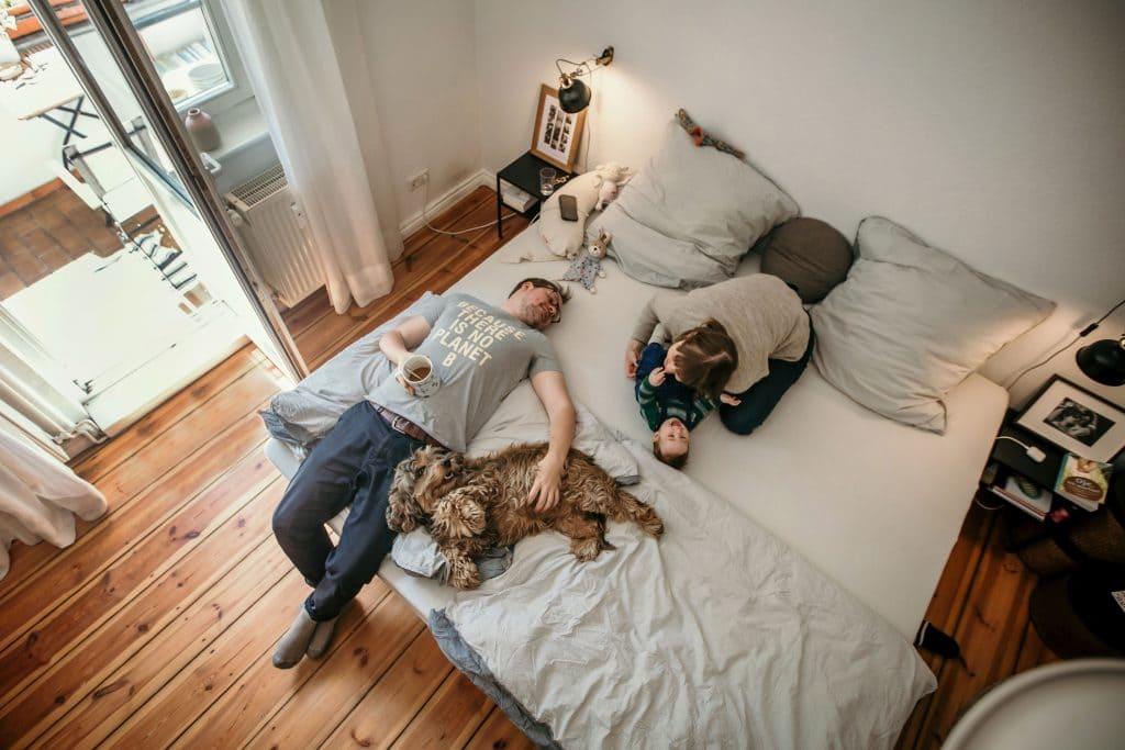 Familie mit Hund liegen auf Ehebett Foto von oben